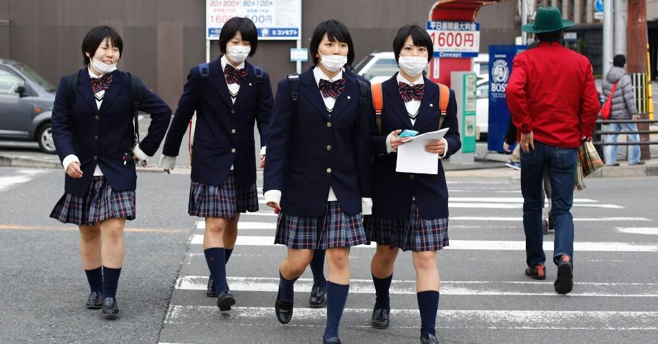 19.nov.2014 - estudantes com os rostos protegidos contra a poluição cruzam a rua na hora do almoço em Kyoto, Japão