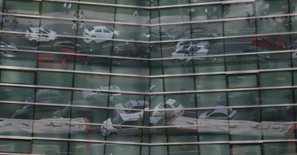 19.nov.2014 - Reflexo em janelas de prédio mostra o trânsito congestionado na avenida Brigadeiro Faria Lima, próximo a Rua Tabapuã, durante o fim de tarde em São Paulo
