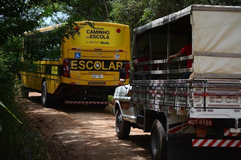 Em estrada de acesso ao sítio Recanto, ônibus escolares e paus-de-arara dividem espaço em pista vicinal