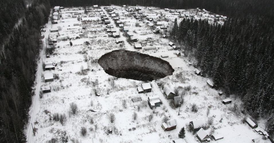 20.nov.2014 - Imagem área mostra buraco enorme, de 30 por 40 metros, que foi encontrado perto de uma mina de potássio na região de Perm, na Rússia. O trabalho foi suspenso no local, que corresponde por um quinto da capacidade de produção da empresa. A mina foi fechada, pois foi detectada uma grande quantidade de intfiltração de água no local. O buraco fica localizado a 3,5 km da mina, sobre uma outra mina abandonada, e ainda será investigado qual é a relação da infiltração de água em com o buraco