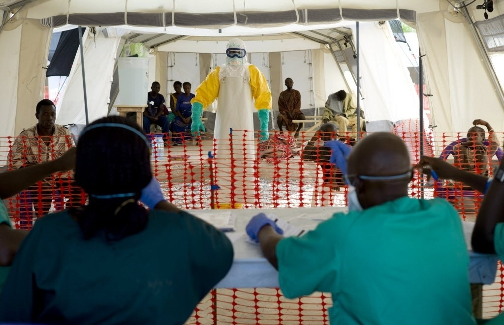 21.nov.2014 - Funcionário de saúde com roupa de proteção atende paciente infectado pelo vírus ebola em Patrice, perto de Macenta, na Guiné, nesta sexta-feira (21). De acordo com a OMS (Organização Mundial de Saúde),  5.420 pessoas morreram infectados pelo vírus em oito países