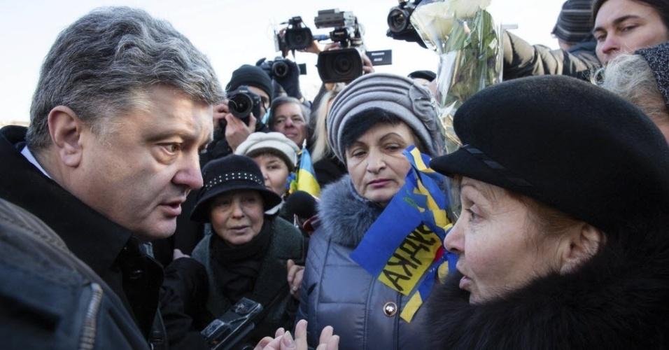 21.nov.2014 - O presidente da Ucrânia, Petro Poroshenko, conversa com mulher durante evento em homenagem aos mortos das manifestações da praça de Maidan, que completam um ano. Poroshenko foi vaiado por parentes de dezenas de vítimas que morreram em confrontos com a polícia na época. Os protestos de Maidan levaram à queda do governo pró-russo de Viktor Yanukovich em fevereiro de 2014