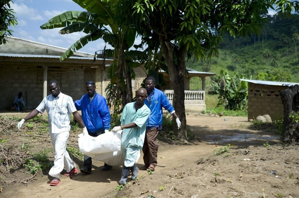 21.nov.2014 - Trabalhadores da Cruz Vermelha carregam o corpo de uma vítima de ebola em Patrice, perto de Macenta, na Guiné, nesta sexta-feira (21). De acordo com a OMS (Organização Mundial de Saúde),  5.420 pessoas morreram infectados pelo vírus em oito países