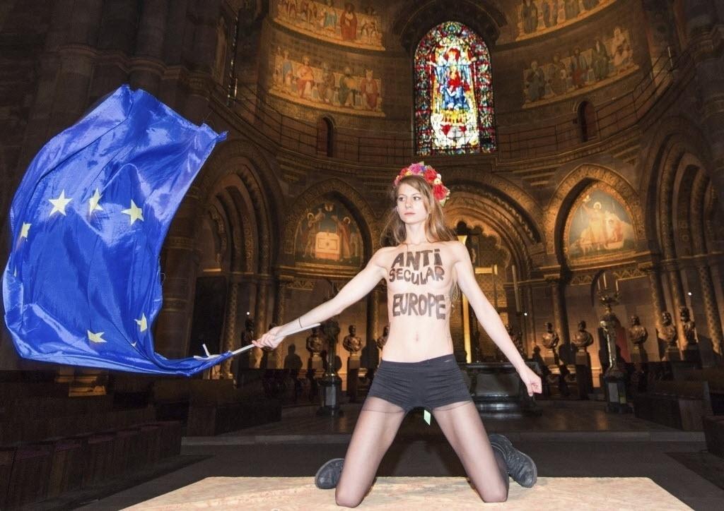 24.nov.2014 - Ativista do grupo Femen protesta segurando uma bandeira da União Europeia (UE), na Catedral de Notre Dame, em Estrasburgo, na França. O protesto é contra a visita do papa Francisco ao Parlamento Europeu, que deve acontecer na terça-feira (25)