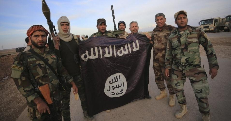 24.nov.2014 - Combatentes xiitas iraquianos posam com uma bandeira do Estado Islâmico (EI) após combaterem na linha de frente em Jalawla, na província de Diyala. As forças iraquianas disseram neste domingo (23) que retomaram duas cidades ao norte de Bagdá, liberando a estrada principal que vai da capital para o Irã