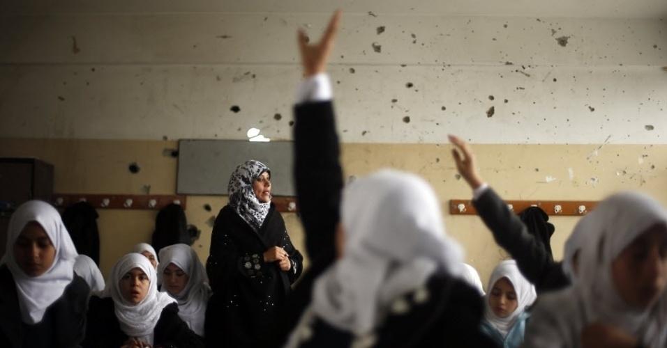 24.nov.2014 - Estudantes palestinas assistem a uma aula em escola que testemunhas dizem ter sido atingida por um bombardeio israelense no mais recente conflito entre Israel e o Hamas, em um dia chuvoso no leste da faixa de Gaza, nesta segunda-feira (24)