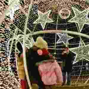 24.nov.2014 - Grupo tira foto dentro de uma bola de Natal iluminada com 20.000 luzes de LED, nesta segunda-feira (24), em Ludwigshafen, na Alemanha - Uwe Anspach/EFE
