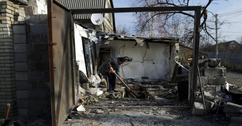 24.nov.2014 - Homem limpa a garagem danificada por um bombardeio na aldeia Krasnyi Pakhar, perto de Donetsk, no leste da Ucrânia. Cerca de 40 bombas atingiram a aldeia no início da manhã