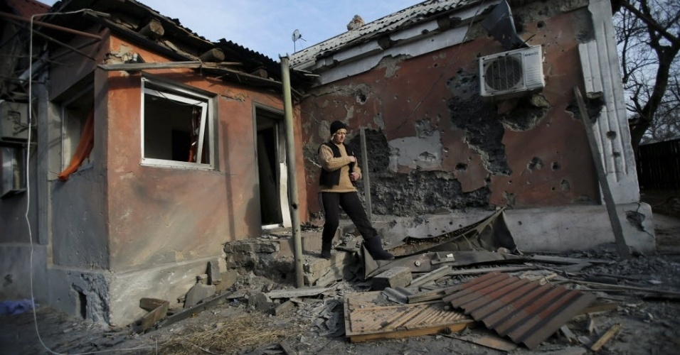 24.nov.2014 - Mulher anda na frente de sua casa que foi danificada pelo bombardeio na vila Krasnyi Pakhar, perto de Donetsk, no leste da Ucrânia. Cerca de 40 bombas atingiram a aldeia no início da manhã