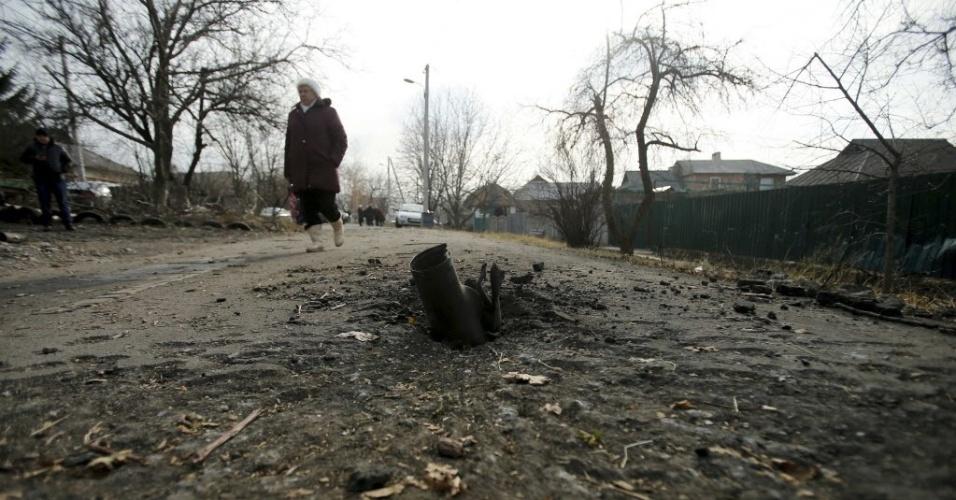 24.nov.2014 - Mulher caminha ao lado de uma granada que explodiu na vila Krasnyi Pakhar, perto de Donetsk, no leste da Ucrânia. Cerca de 40 bombas atingiram a aldeia no início da manhã