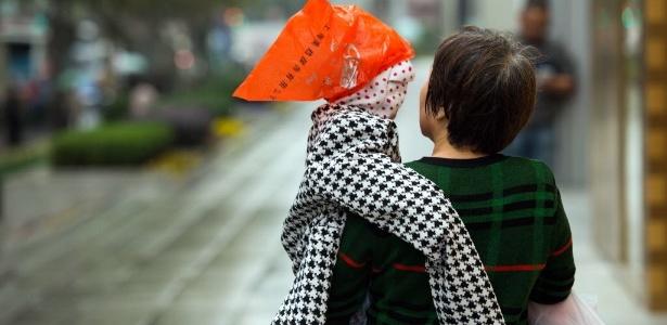 24.nov.2014 - Mulher carrega bebê coberto com uma máscara para protegê-lo da poluição e um plástico na cabeça para o proteger da chuva em Xangai, na China