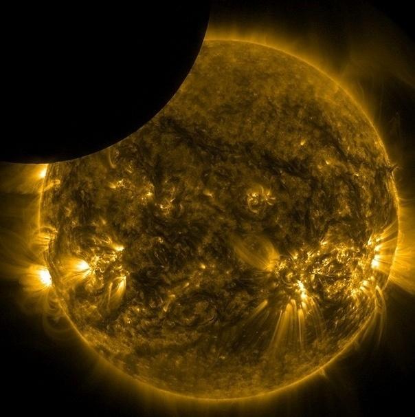 25.nov.2014 - Lua, totalmente escura na imagem, esconde parcialmente a visão do Sol. Os astros foram vistos a partir do observatório Solar Dynamics, ou SDO, da Nasa, no dia 22 de novembro