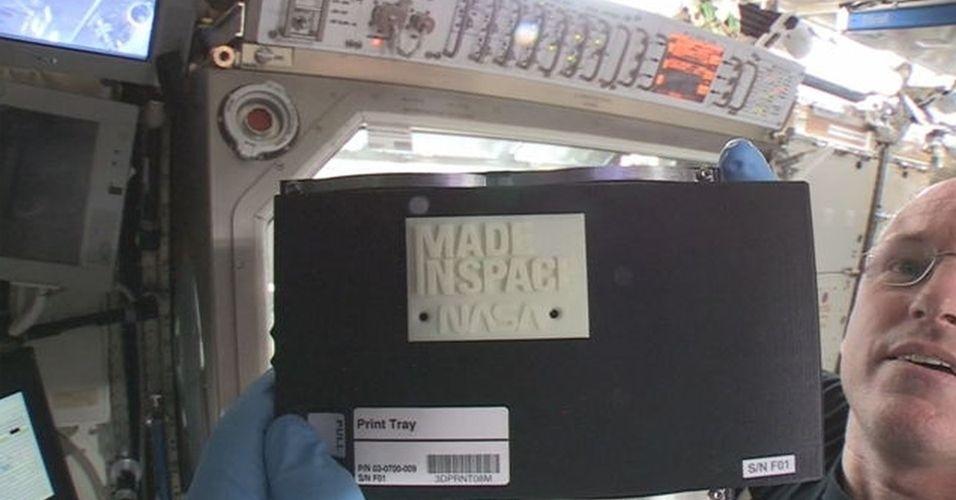 26.nov.2014 - A Nasa divulgou a imagem acima, que mostra o primeiro objeto feito pela impressora 3D enviada à ISS (Estação Espacial Internacional) neste ano. A placa levou pouco mais de uma hora para ser produzida, e os comandos foram enviados por uma base da Terra. O objetivo da ferramenta é produzir peças para a Estação, de maneira que não seja mais necessário enviar tudo a partir da Terra
