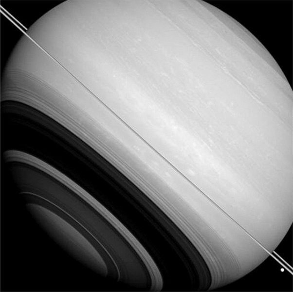 26.nov.2014 - Saturno está cercado por seus anéis (visto quase de lado nesta imagem), bem como pelas luas Tétis (a grande massa brilhante perto do canto inferior direito da imagem) e Mimas (não retratada na imagem). Embora os anéis e luas maiores do planeta orbitem, principalmente, perto do plano equatorial, esta imagem mostra que nem todos eles se encontram precisamente nesta posição. Parte da razão que Mimas (396 km de diâmetro) e Tétis (1.062 km de diâmetro) estão acima e abaixo do plano do anel, porque suas órbitas são ligeiramente inclinadas (cerca de 1 a 1,5 graus) em relação aos anéis