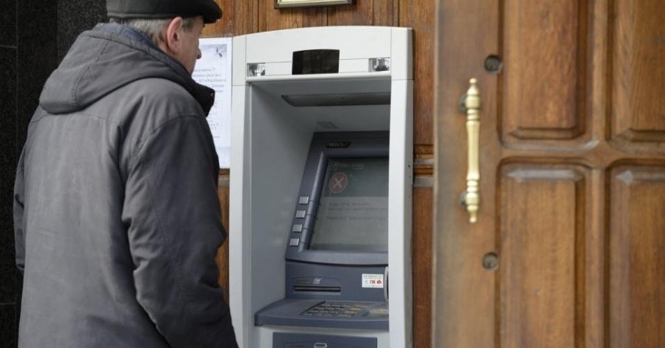 26.nov.2014 - Um homem tenta usar uma máquina para tirar dinheiro da ATM, mas não há caixas eletrônicos funcionando nesta quarta-feira (26) na cidade ucraniana de Donetsk. A maioria das lojas locais não aceita pagamento em cartões de crédito depois que Kiev suspendeu as atividades bancárias da região leste da Ucrânia, controlada por separatistas pró-Rússia