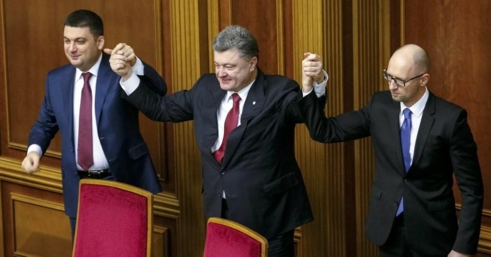 27.nov.2014 - O presidente da Ucrânia Petro Poroshenko segura as mãos do recém-nomeado primeiro-ministro Arseny Yatseniuk (à direita) e o recém-nomeado presidente do Parlamento Volodymyr Groysman durante a sessão de abertura em Kiev
