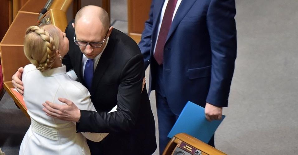 27.nov.2014 - O primeiro-ministro ucraniano Arseniy Yatsenyuk (à dir.) cumprimenta a chefe do partido Batkivshchyna Yulia Tymoshenko (à esq.) durante a cerimônia de posse do novo Parlamento durante a abertura de uma sessão em Kiev, na Ucrânia, nesta quinta-feira (27). O Parlamento se reuniu para a sua primeira sessão desde que o partido pró-ocidentais obteve uma vitória esmagadora nas eleições de outubro