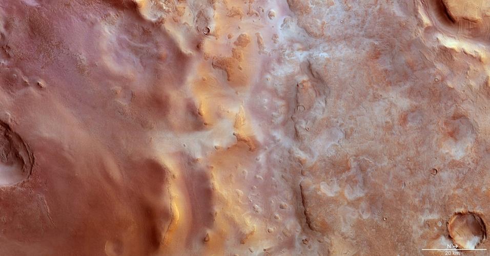 """28.nov.2014 - Imagem obtida por missão da ESA (agência espacial europeia) em Marte mostra a variedade de formas de relevo de Hellas Chaos, na parte central da bacia de Hellas, no hemisfério Sul do planeta vermelho. A região é composta por grandes crateras com dunas e depressões, além da presença de dióxido de carbono congelado. Para os cientistas, as características do relevo local são típicas de terrenos """"periglaciais"""", pois se desenvolvem como resultado da contração e relaxamento durante os ciclos de congelamento e descongelamento da região"""