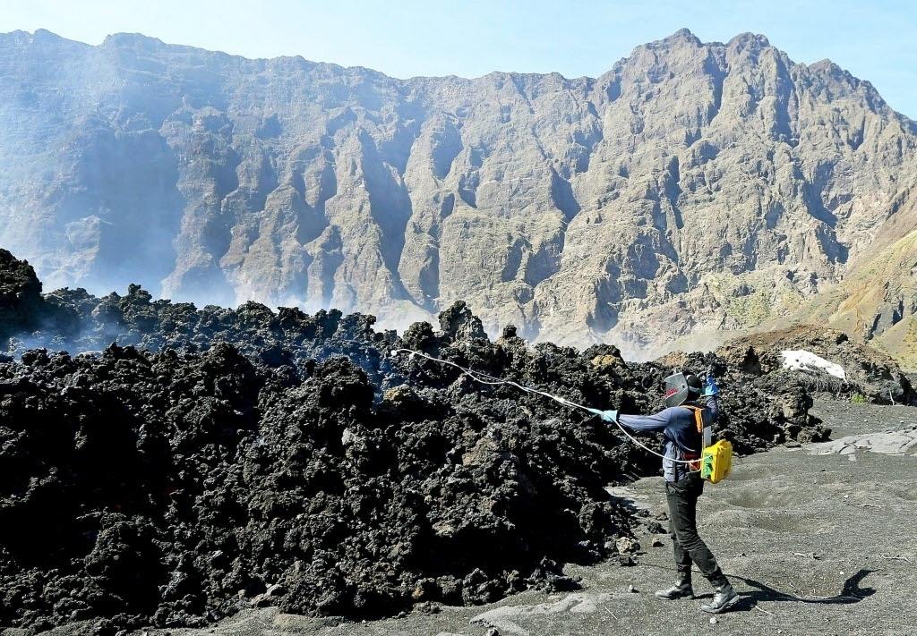 30.nov.2014 - Geólogo do Serviço Nacional de Proteção Civil de Cabo Verde, na África, usa equipamento especial para medir a emissão de gases da atividade vulcânica na Ilha do Fogo, neste domingo. O vulcão da ilha ficou mais ativo nos últimos dias e lançou lava para fora em explosões intensas