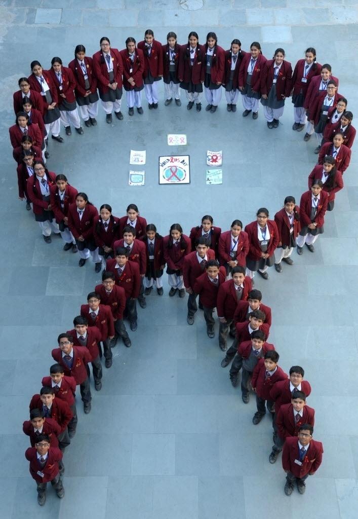 1º.dez.2014 - Alunos de escolas indianas posam para uma campanha de conscientização para marcar o Dia Mundial da Luta contra a Aids, em uma escola em Amritsar