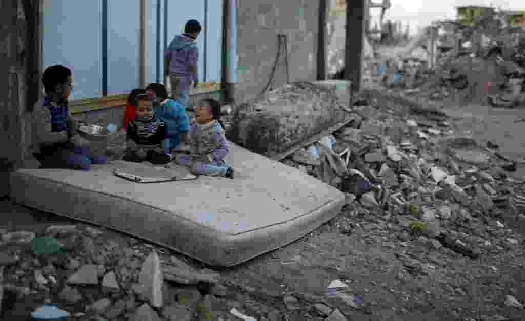 1º.dez.2014 - Crianças palestinas brincam em cima de colchão perto das ruínas de casas que foram destruídas por bombardeios israelenses durante conflito entre Israel e Hamas, no leste da faixa de Gaza, nesta segunda-feira (1º). De acordo com o ministro da Habitação, Mufeed al-Hasayna, é preciso 8.000 toneladas de cimento por dia para reconstruir os locais atingidos durante o combate, no entanto, Israel só deixa passar, no máximo, 2.000. Nesse ritmo, segundo ele, a reconstrução levaria mais de 30 anos - Mohammed Salem/Reuters