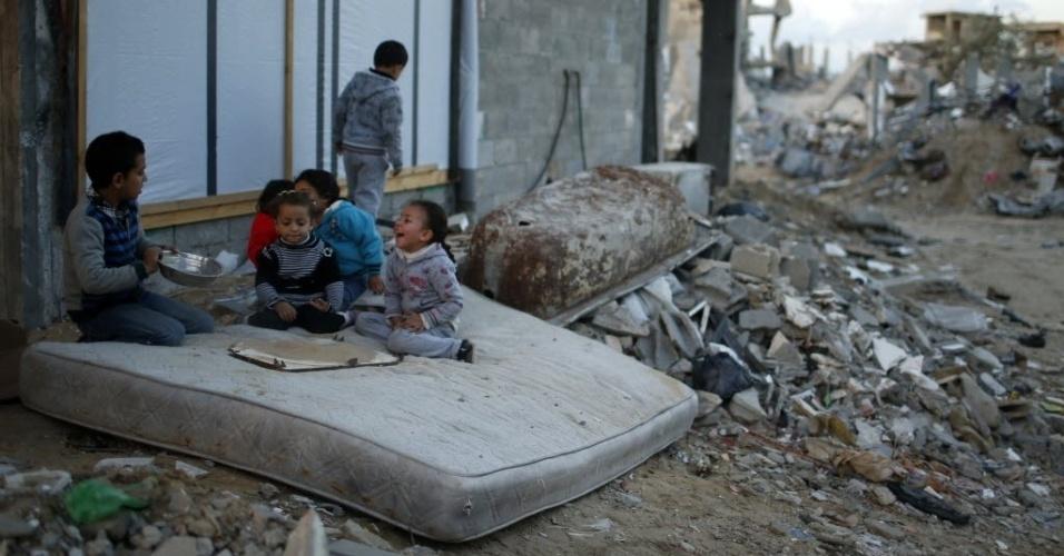 1º.dez.2014 - Crianças palestinas brincam em cima de colchão perto das ruínas de casas que foram destruídas por bombardeios israelenses durante conflito entre Israel e Hamas, no leste da faixa de Gaza, nesta segunda-feira (1º). De acordo com o ministro da Habitação, Mufeed al-Hasayna, é preciso 8.000 toneladas de cimento por dia para reconstruir os locais atingidos durante o combate, no entanto, Israel só deixa passar, no máximo, 2.000. Nesse ritmo, segundo ele, a reconstrução levaria mais de 30 anos