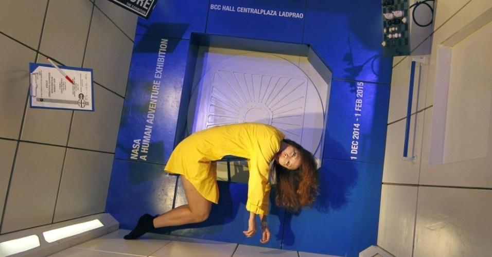 """1º.dez.2014 - Visitante posa dentro de um módulo livre de gravidade durante a exposição itinerante """"Nasa - A aventura humana"""", em Bancoc (Tailândia). A exposição inclui 350 artefatos originais e pode ser visitada a partir desta segunda-feira (1º) até 1º de fevereiro de 2015"""