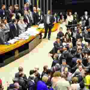 """2.dez.2014 - A sessão do Congresso Nacional para votar a manobra fiscal a que o governo recorreu para tentar fechar as contas de 2014 foi marcada pela troca de socos, empurra-empurra e muita gritaria. Após a interrupção de manifestantes, que gritavam """"PT roubou"""" e """"vá para Cuba"""", o presidente do Congresso, senador Renan Calheiros (PMDB-AL), mandou esvaziar as galerias do plenário, mas congressistas da oposição fizeram um cordão de isolamento para tentar impedir ação da Polícia Legislativa. A votação foi suspensa - Gustavo Lima / Câmara dos Deputados"""