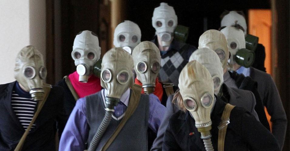 2.dez.2014 - Alunos de uma escola localizada na aldeia de Krevo, noroeste de cidade de Minsk (Bielorrússia - Leste Europeu), usam máscaras de gás durante um treinamento de segurança contra incêndio