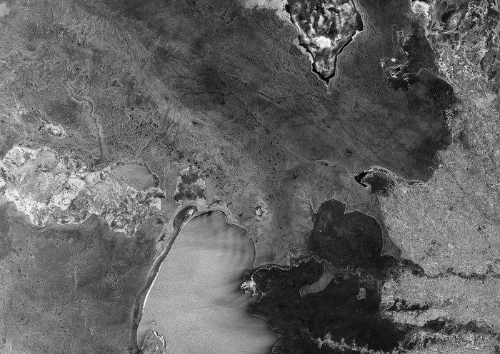 2.dez.2014 - Esta imagem feita por satélite mostra a região de fronteira do semiárido entre o Usbequistão (em cima) e Turquemenistão (parte inferior). A parte norte do lago Sarygamysh, que fica na fronteira, pode ser vista no centro inferior da imagem. A parte superior da imagem mostra a parte sul do lago Chimboy. Em contraste com esta região do semiárido, a terra irrigada é vista no lado direito da imagem. Esta imagem foi transmitida por quase 36.000 km ao longo do espaço por um laser para o satélite em órbita, que enviou os dados para a Terra. Tudo isso aconteceu em questão de momentos. A demonstração abre o caminho para a utilização de tecnologia a laser para entregar grandes volumes de dados quase que instantaneamente, ajudando na segurança marítima e prevenindo desastres naturais
