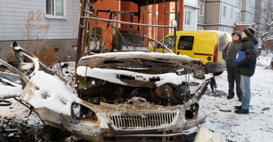 2.dez.2014 - Moradores observam um ônibus que foi bombardeado em Donetsk, na Ucrânia. Os insurgentes da região se reunirão nesta terça-feira (2) com representantes do Estado-Maior das tropas ucranianas, na capital da região, para tentar chegar a um acordo de cessar-fogo total