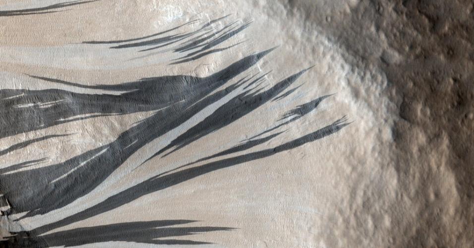 3.dez.2014 - Declividades escuras são visíveis na região de Acheron Fossae, cercada por dunas, em Marte. Com a curadoria de artistas, fotógrafos e editores de fotografia, a Nasa reuniu uma série de imagens para compor a
