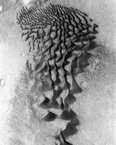 3.dez.2014 - Dunas escuras formam fitas e laços na cratera Bunge, em Marte. A formação é resultado dos ventos que sopram na direção da cratera. A imagem foi obtida em janeiro de 2006 pela sonda Mars Odyssey da Nasa (agência espacial americana). Com a curadoria de artistas, fotógrafos e editores de fotografia, a Nasa reuniu uma série de imagens para compor a