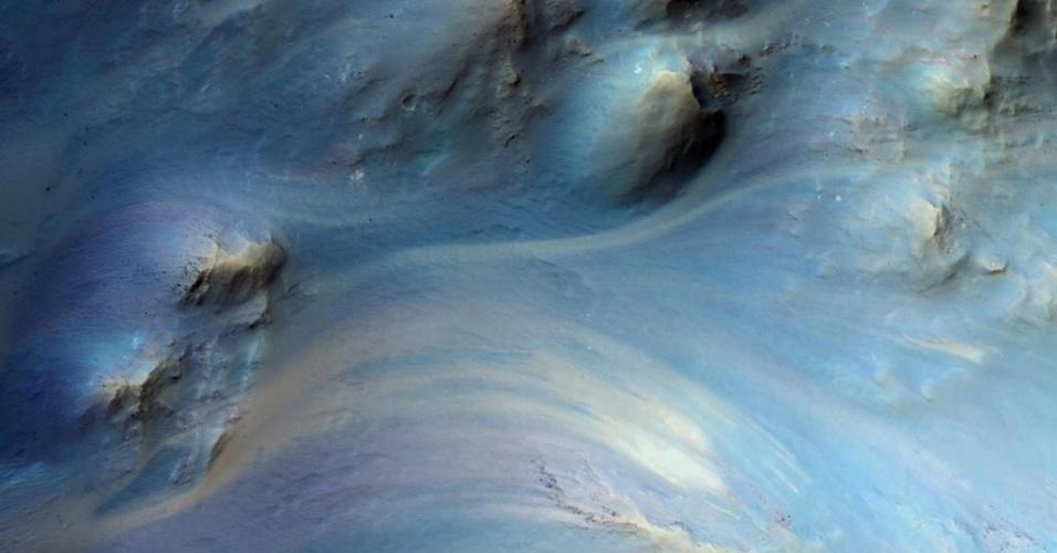 3dez.2014 - Imagem exibe poço central de uma cratera de impacto em um planalto antigo de Marte. Com a curadoria de artistas, fotógrafos e editores de fotografia, a Nasa reuniu uma série de imagens para compor a