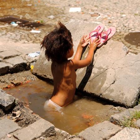 Foto de 2014 mostra menina tomando banho em bueiro aberto na rua Luís de Camões, no centro do Rio de Janeiro - Marcelo Piu / Ag. O Globo