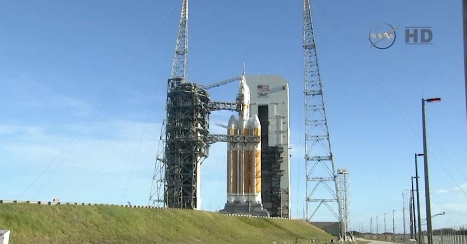 4.dez.2014 - Durante transmissão ao vivo, Nasa (agência espacial americana) exibe o foguete Delta 4, que carrega a cápsula Orion, na plataforma de lançamento em Cabo Canaveral, na Florida. O lançamento da cápsula, que estava marcado para às 7h05 desta quinta-feira (10h05 no horário de Brasília), precisou ser adiado em algumas horas devido aos ventos no local. A espaçonave não tripulada dará duas voltas em torno da Terra e alcançará 5.800 quilômetros de altitude, o que é 15 vezes mais distante que o ponto de órbita da ISS (Estação Espacial Internacional). Quando a cápsula espacial retornar à Terra, um navio da Marinha a retirará do oceano