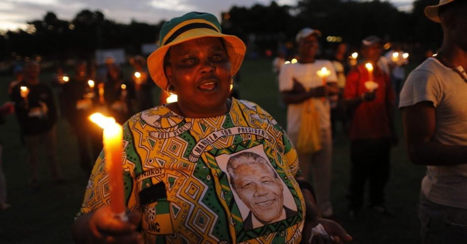 5.dez.2014 - Mulher vestida com camiseta de Nelson Mandela carrega vela durante cerimônia em Soweto em homenagem ao líder sul-africano, cuja morte completa um ano nesta sexta-feira (5). Um dos maiores adversários do regime segregacionista do apartheid, Mandela morreu aos 95 anos devido à complicações de problemas respiratórios