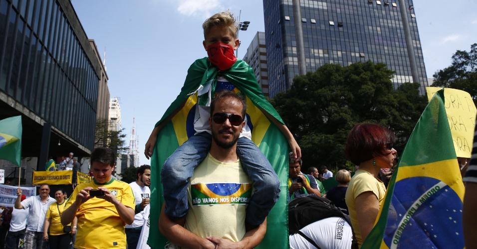 6.dez.2014 - Boa parte dos manifestantes que participam do ato contra a presidente reeleita Dilma Rousseff na Avenida Paulista trazem bandeiras do Brasil nas costas e faixas vermelhas sobre a boca