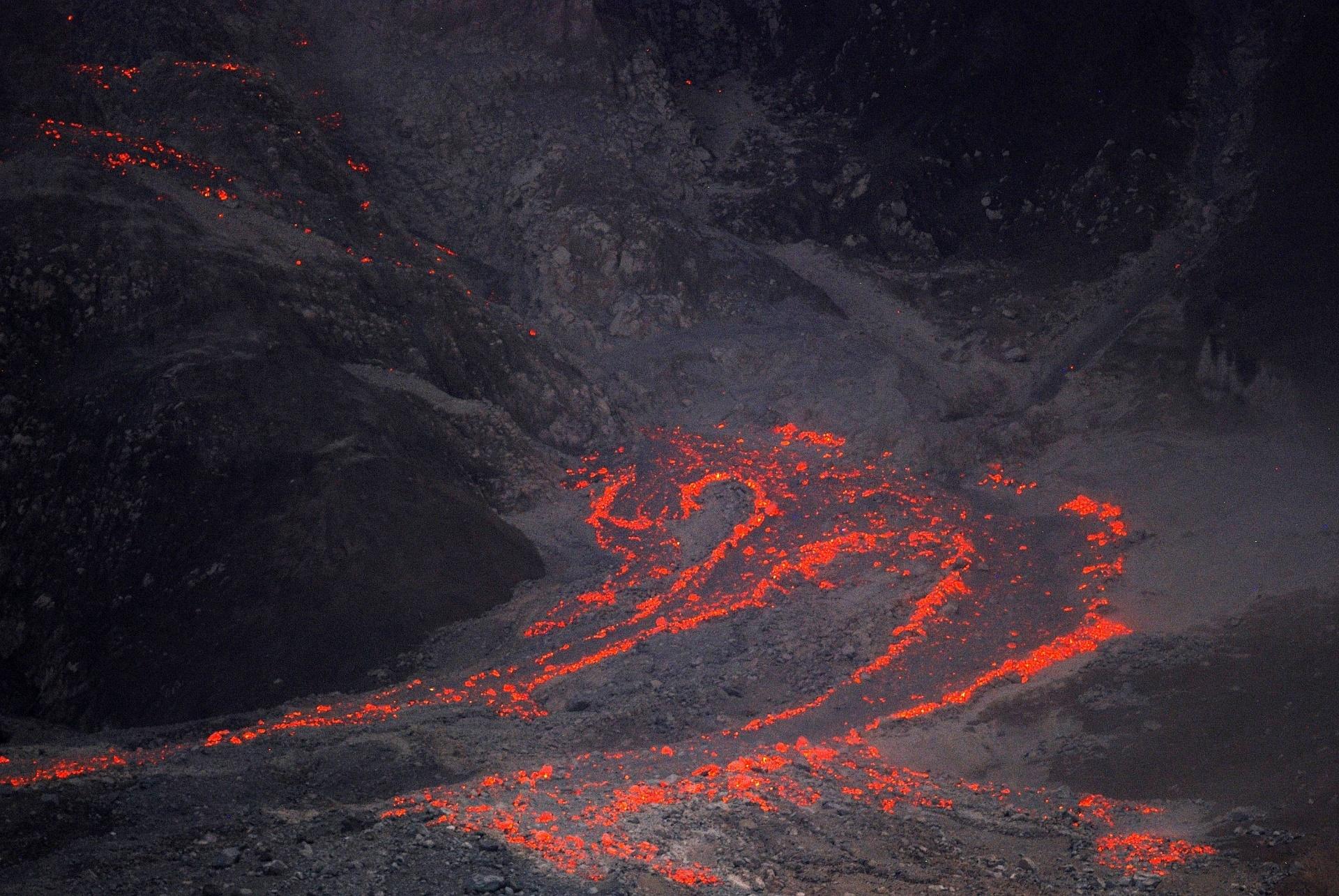 7.dez.2014 - Lava desce da cratera do vulcão Monte Sinabung, em Karo, província da ilha indonésia de Sumatra. O governo local removeu moradores que residiam em áreas de risco próximas do vulcão. Ao todo, 17 pessoas moreram desde fevereiro, quando o vulcão entrou em erupção