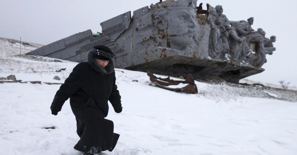 7.dez.2014 - Mulher caminha próximo a um monumento em homenagem à atuação do Exército Vermelho soviético na Segunda Guerra Mundial, em Savur-Mohyla, no leste da Ucrânia. O monumento foi danificado nos conflitos entre rebeldes pró-Rússia e ucranianos