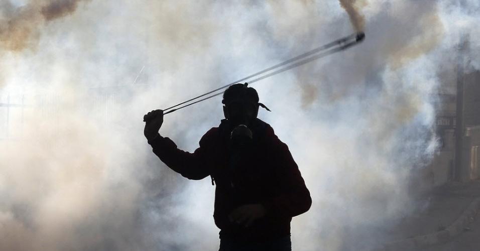 11.dez.2014 - Manifestante palestino usa um estilingue para atirar de volta uma bomba de gás lacrimogêneo disparada por soldados israelenses durante confrontos após o funeral do ministro palestino Ziad Abu Ein, perto da cidade de Ramallah, na Cisjordânia. O líder morreu durante outro protesto na Cisjordânia, o que elevou as tensões com Israel