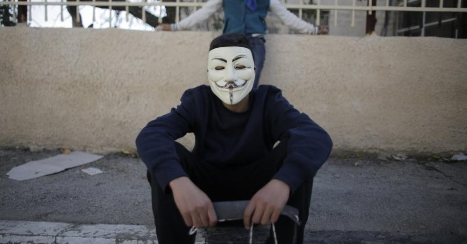 11.dez.2014 - Manifestante palestino, usando uma máscara, descansa durante confrontos com tropas israelenses, após o funeral do ministro palestino Ziad Abu Ein, perto da cidade de Ramallah, na Cisjordânia