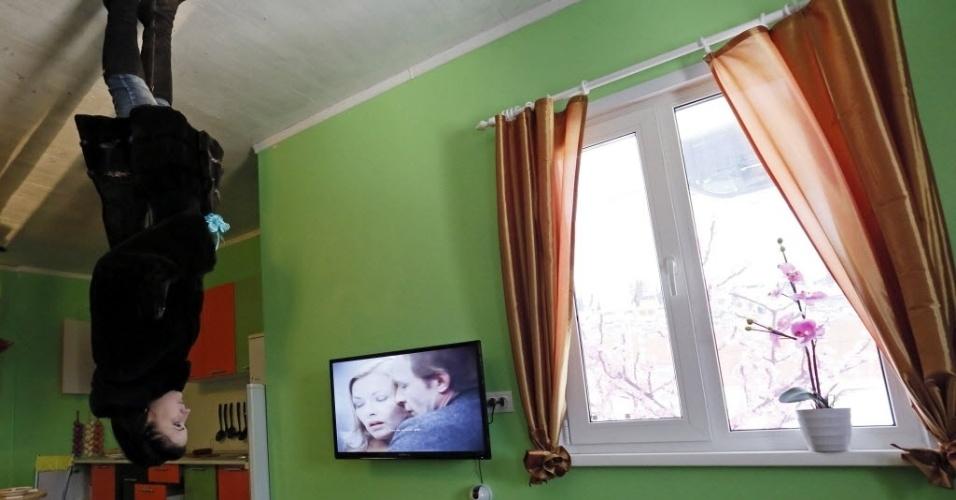 14.dez.2014 - Uma mulher visitou neste domingo (14) uma casa construída de cabeça para baixo na cidade de Krasnoyarsk, na Rússia. O imóvel foi feito para chamar atenção de turistas e para divertir os moradores locais