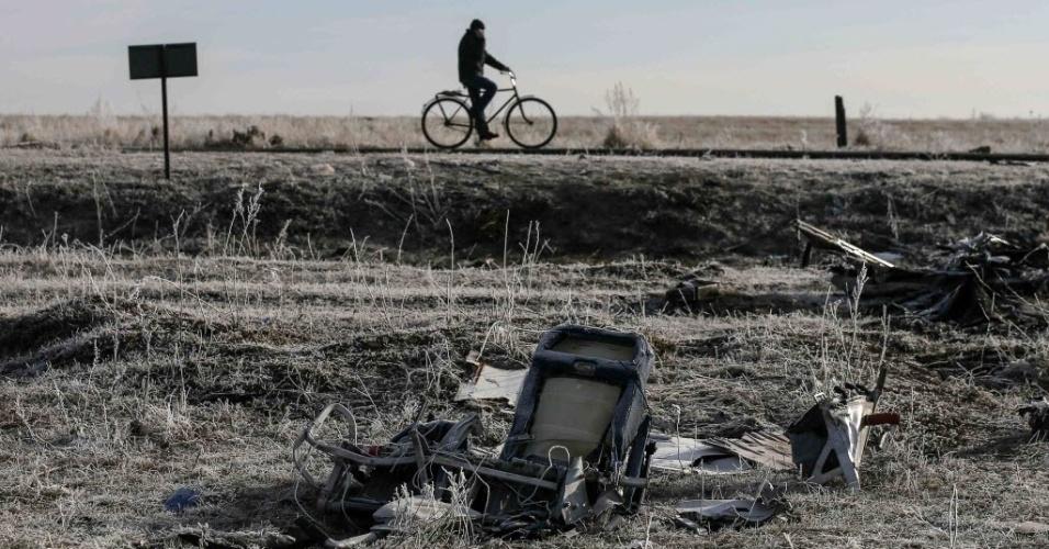 15.dez.2014 - Homem passa de bicicleta perto dos destroços do voo MH17, da Malaysia Airlines, no local da queda perto da vila de Hrabove, na região de Donetsk, na Ucrânia, nesta segunda-feira (15)