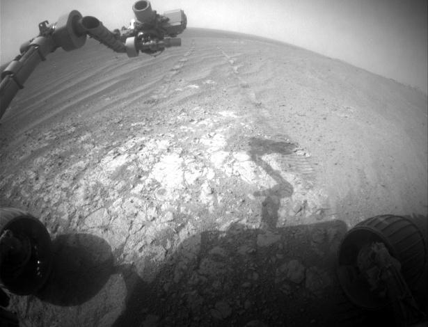 """15.dez.2014 - Sonda Opportunity da Nasa avança para o sul da borda oeste da cratera Endeavour, em Marte, em imagem tirada no dia marciano 3854 (26 de novembro na Terra). O equipamento fez pausa para investigar um afloramento brilhante na cratera. A cena inclui o braço robótico da Opportunity, chamado de """"dispositivo de implantação instrumento"""", no canto superior esquerdo. Também é possível ver uma das rodas da sonda"""