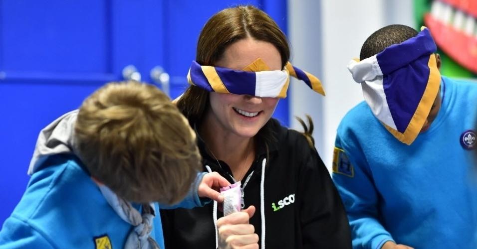 16.dez.2014 - A duquesa de Cambridge, Kate Middleton, usa uma venda enquanto é ajudada por um garoto a confeitar um cupcake em uma reunião com as crianças da recém-criada 23ª Colônia de Escoteiros Poplar Beaver, no leste de Londres, durante evento que promove a conscientização sobre a deficiência, nesta terça-feira (16)
