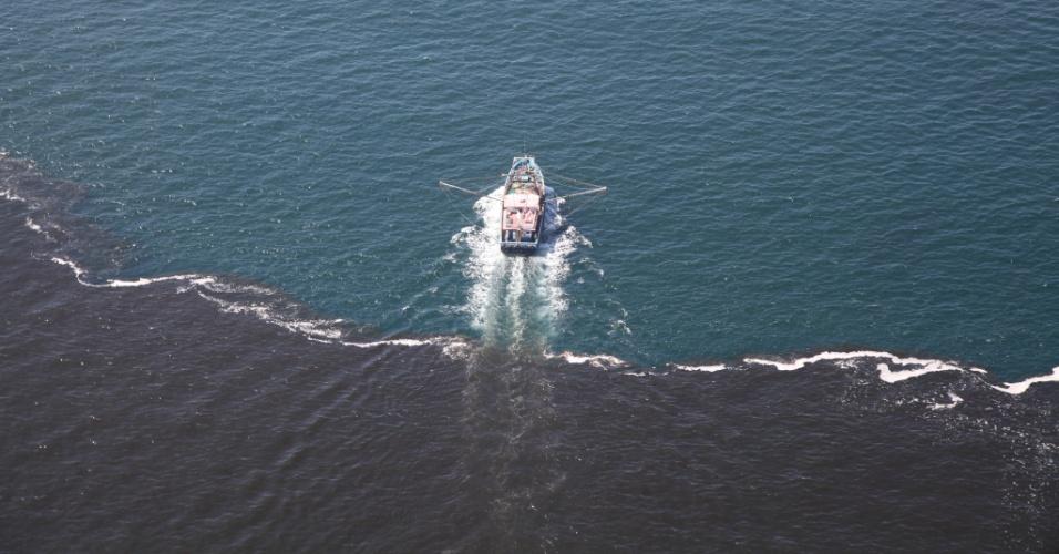 16.dez.2014 - Embarcação navega enquanto mancha escura é vista na Baía de Guanabara, na cidade do Rio de Janeiro