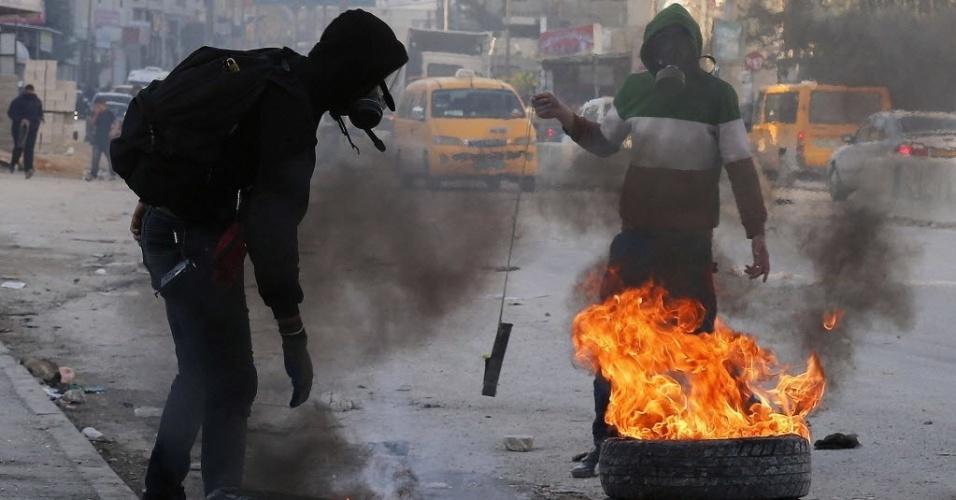16.dez.2014 - Palestino colocam fogo em pneus durante confrontos com tropas israelenses após o funeral do palestino Mahmoud Adwan, no ponto de inspeção de Qalandia, próximo a Ramallah, na Cisjordânia, nesta terça-feira (16). Soldados israelenses atiraram contra Mahmoud Adwan, que more, após invasão de um campo de refugiados ocupado na Cisjordânia, afirmaram testemunhas