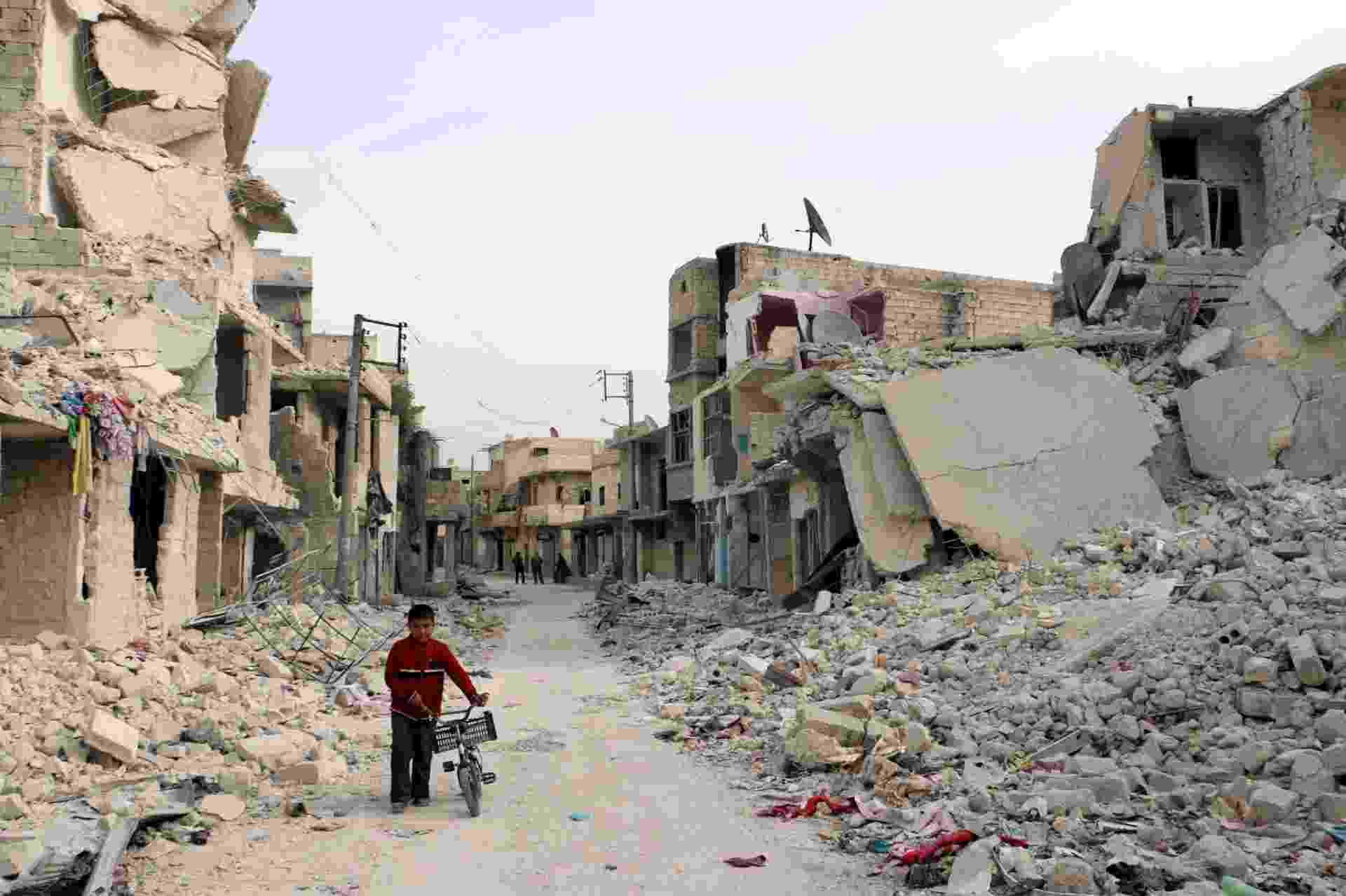 13.nov.2014 - Menino caminha com bicicleta em bairro destruído de Aleppo, na Síria - Baraa al-Halabi/AFP