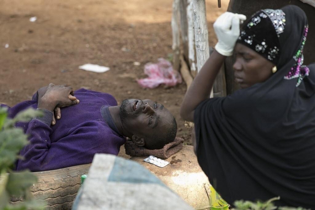 17.dez.2014 - Adama Tarawallie fica junto ao marido Ibrahim, 31, que está com suspeita de ebola, enquanto esperam para serem transportados para um hospital, no oeste de Freetown, em Serra Leoa, nesta quarta-feira (17). O aumento de casos no país diminuiu, apesar de 327 novos casos terem sido confirmados na semana passada, segundo a OMS